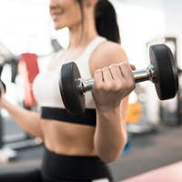 Woman Training with Weights in Gym
