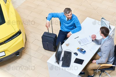 Mature Man Renting Car in Showroom