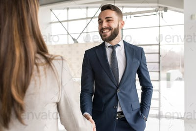 Smiling Car Salesman Shaking Hands with Client