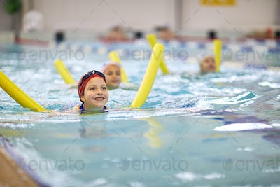 Little girl with swimming noodle