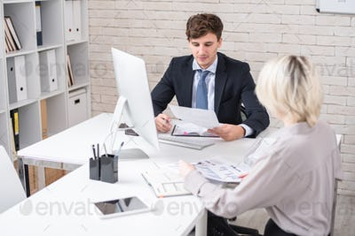 Business People Discussing Statistics during Meeting in Office