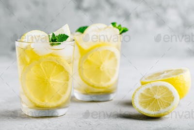 Lemonade with lemon, mint and ice cubes in glass on gray stone background.