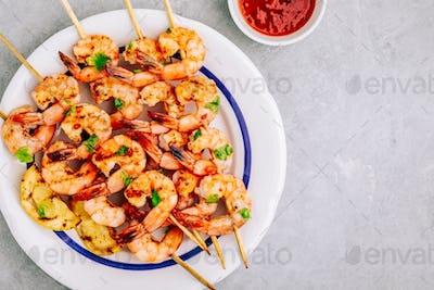Sweet Chili Shrimp Skewers with lemon and parsley on gray stone background