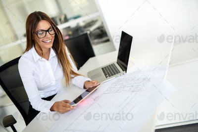 Young female architect working with computer and blueprints