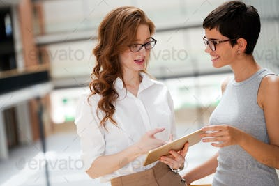 Portrait of two young attractive businesswomen talking on break