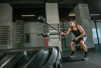 A muscular male athlete doing workout at the gym