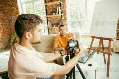 Two young male bloggers with professional camera recording video interview at home