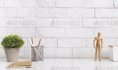 Table with stationery and wooden mannequin in modern office