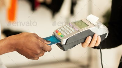 Customer paying for clothes by credit card in designer boutique