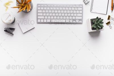 Office desk with keyboard and supplies on white table