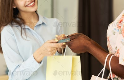 Shop Assistant Giving Package And Credit Card To Client, Cropped