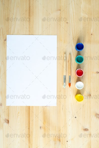 Blank sheet of paper, two paintbrushes and row of colorful paints or gouaches