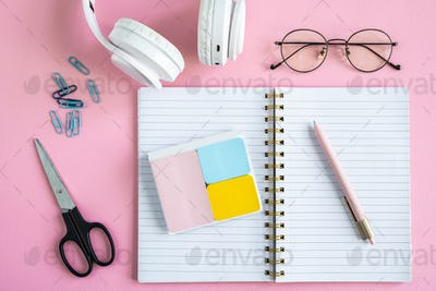 Open notebook, erasers, pen, clips, scissors, eyeglasses and headphones