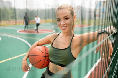 Young successful female basketball player with ball looking at you