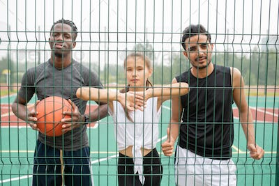 Young active woman and two men in sportswear standing by basketball net