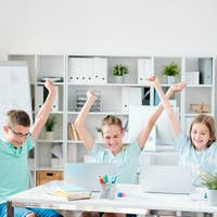 Three successful schoolmates keeping their hands raised while expressing joy