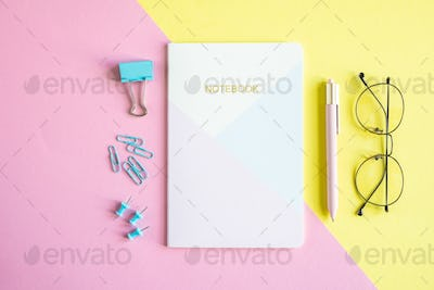 Several pins, clip, notebook, pen and eyeglasses on pink and yellow background