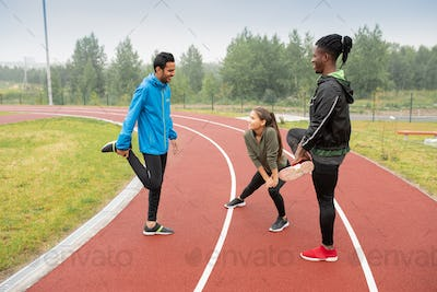 Group of young intercultural athletes doing wam-up exercises on racetracks