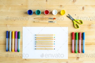 Colorful gouaches, paintbrushes, scissors, crayons on paper and highlighters
