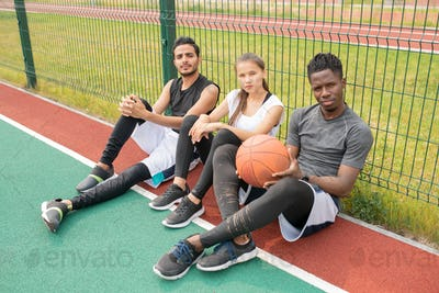 Three young athletes in sportswear sitting on outdoor basketball court by net