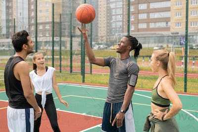 Happy young African sportsman holding ball on forefinger among friends