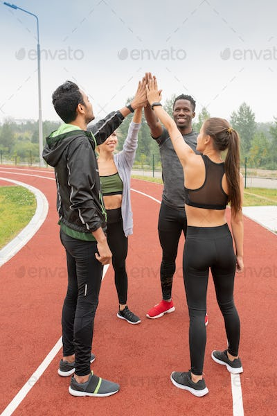 Intercultural friends in sportswear touching by hands while standing in circle