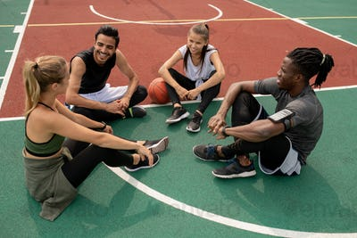 Happy young intercultural friends discussing last game of basketball