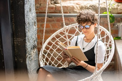Contemporary young woman in casualwear and eyeglasses reading novel