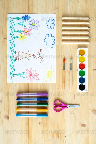 Overview of pencil drawing surrounded by artwork supplies on wooden table