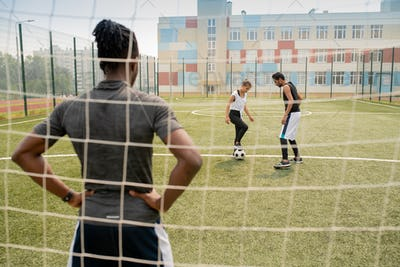 Rear view of young African sportsman standing by net and looking at two players