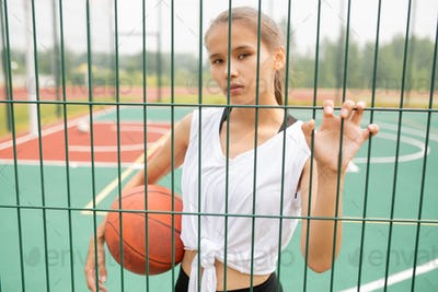 Pretty girl in activewear holding ball while looking at you through sports net