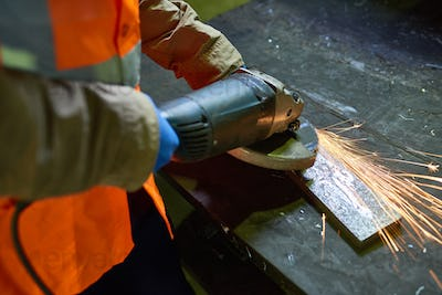 Man Working with Metal at Factory