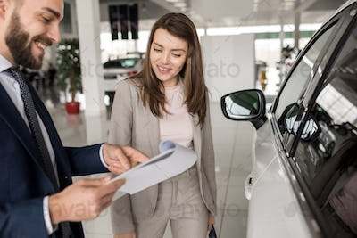Beautiful Woman Talking to Salesman in Car Showroom