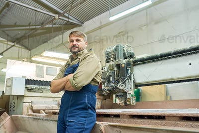 Mature Factory Worker Posing with Cutting Machine