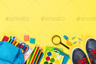 School backpack with stationery on yellow background