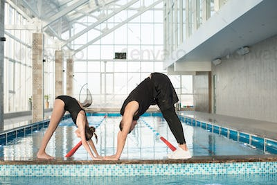 Trainer showing exercise to little swimmer