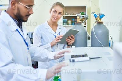 Smiling female assistant asking doctor of medicine