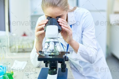 Busy female biologist using microscope in lab