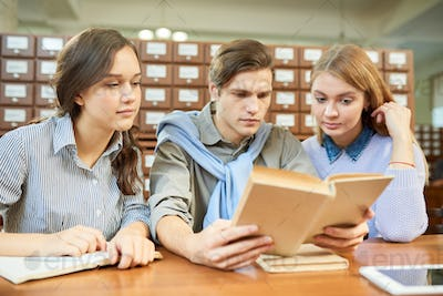 College students reading textbook in library