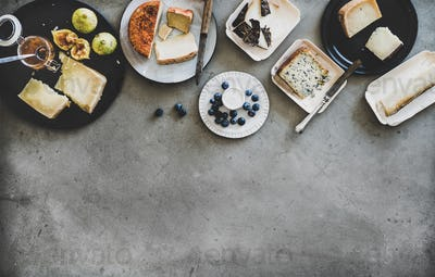 Variety of snacks, jam and cheeses over grey background