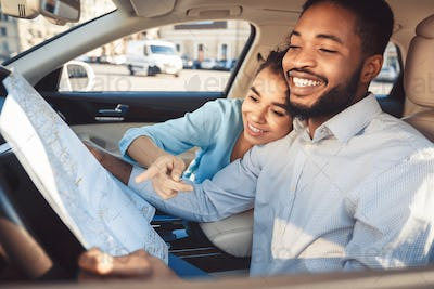 Happy young couple with map in car