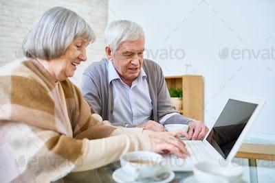 Elderly friends with laptop in nursing home