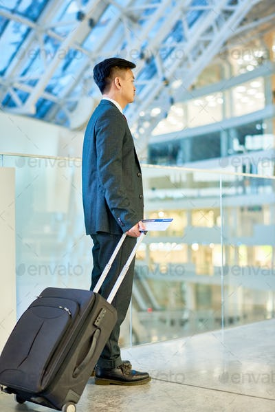 Asian Businessman Carrying Suitcase