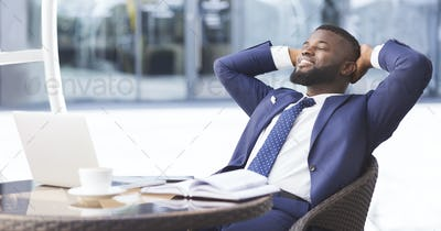 Cheerful black businessman relaxing in outdoor cafe, panorama
