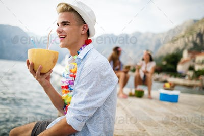Young happy people with drinks relaxing on the beach