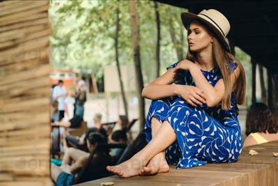 Young attractive dreamy woman in blue dress and hat barefoot thoughtfully looking aside in city park