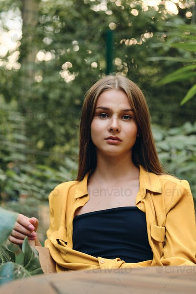 Young gorgeous brown haired woman in yellow shirt seriously looking in camera sitting in city park