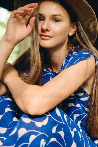 Young beautiful woman in blue dress and hat dreamily looking in camera in city park