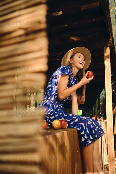Attractive cheerful girl in blue dress and hat eating peach happily sitting on wooden fence in park