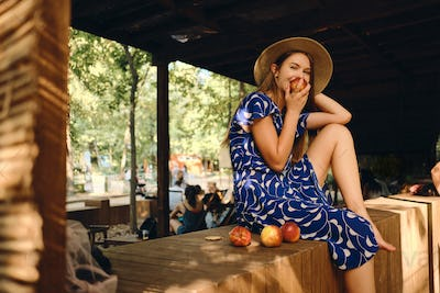 Young pretty woman in dress and hat barefoot eating peach joyfully looking in camera in city park